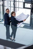 Portrait of business colleagues standing with blueprint in corridor Royalty Free Stock Photo