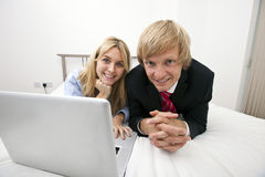 Portrait of business couple with laptop lying on bed Stock Photos