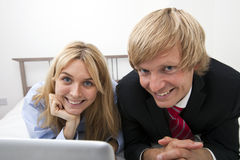 Portrait of business couple lying on bed Stock Image