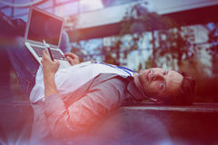 Portrait of business executive listening music while using laptop Royalty Free Stock Images