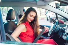 Portrait of business lady, caucasian young woman driver in red summer suit fastening car seat belt while sitting behind the wheel. Car. Safe driving concept royalty free stock photos