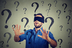 Portrait business man blindfolded stretching his arms out walking through many questions stock photo