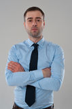 Portrait of business man in blue shirt with folded hands on grey Royalty Free Stock Photos