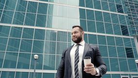 Portrait of a business man drinking coffee and looking around outdoors.  stock video