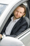 Portrait of business man driving his car. Portrait of an handsome smiling business man driving his car stock images