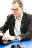 Portrait of a businessman using laptop in office. Royalty Free Stock Photography