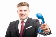 Portrait of business man holding blue telephone receiver. And smiling confident isolated on white background Royalty Free Stock Image