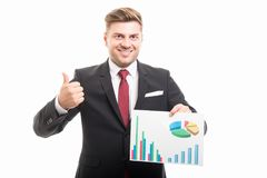 Portrait of business man holding graphs showing like. Or thumb up gesture isolated on white background Royalty Free Stock Photos