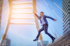 Portrait of business man jumping with arms up celebrate on blurr. Ed city background. Business success concept Stock Photos