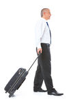 Portrait of business man with luggage. Full body image of mature business man walking with luggage trolley, isolated over white background Royalty Free Stock Photo