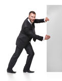 Portrait of business man pushing blank signboard. Portrait of happy smiling young business man pushing blank signboard isolated on white background Royalty Free Stock Photos