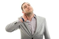 Portrait of business man showing neck pain gesture Royalty Free Stock Photography