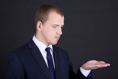 Portrait of business man showing something on his hand Stock Images
