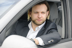 Portrait of business man sitting in car. Portrait of an handsome business man sitting in car royalty free stock images
