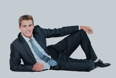 Portrait of business man sitting on the floor isolated over white background. royalty free stock photography
