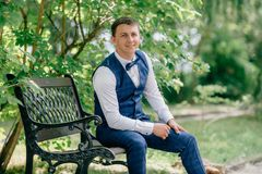 Portrait of business man in suit sitting in park on bench and smiling. The guy is getting ready for the wedding day. Waiting for his bride Stock Image