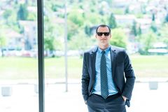 A portrait of a business man with a sun-glasses in his office. C royalty free stock photos