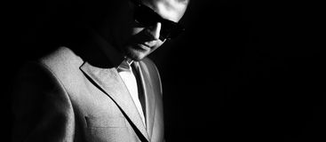 Portrait of business men in sunglasses, low key on the black background, black and white photo stock photography
