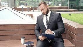 Portrait of a business man taking notes on paper outdoors.  stock video footage