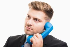 Portrait of business man talking at blue telephone receiver. Isolated on white background Royalty Free Stock Photography