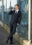 Portrait of a business man talking on cellphone outdoors. Full length portrait of a business man talking on cellphone outdoors Stock Image