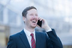 Very happy man talking on the phone. Portrait of a business man talking on the phone, he looks very happy and he`s smiling Royalty Free Stock Photography