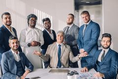 Portrait Of Business men only Meeting Around Table In Office stock images
