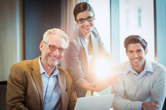 Portrait of business people discussing over digital tablet Royalty Free Stock Images