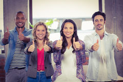 Portrait of business people giving thumbs up in office Stock Image