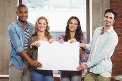 Portrait of business people holding billboard in office. Portrait of business people holding billboard in creative office royalty free stock photos