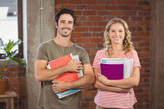 Portrait of business people holding files and folders in office Royalty Free Stock Images