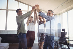 Portrait of business people raising hands together at creative office Stock Photos