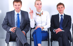Portrait of business people sitting on chairs by office door Stock Photos