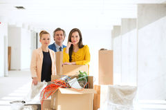 Portrait of business people standing by stacked cardboard boxes at new office Stock Images