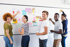 Portrait of business people sticking adhesive note during planning Stock Photos