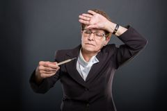 Portrait of business senior having fever holding thermometer. On black background Stock Image