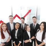 Business Team. Portrait of business team of men and women in office with arrow graph of income growth Stock Image