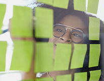 Portrait of a business woman with an afro behind. Friendly african american executive business woman brainstorming using adhesive notes in a modern white office Stock Images