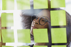 Portrait of a business woman with an afro behind sticky notes in bright glass office Royalty Free Stock Images