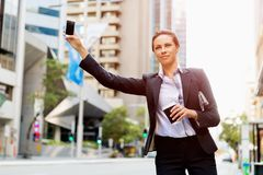 Portrait of business woman catching taxi Royalty Free Stock Image
