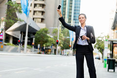 Portrait of business woman catching taxi Stock Images