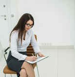 Portrait of business woman with documents and financial charts sitting on a chair in the spacious office. Royalty Free Stock Photos