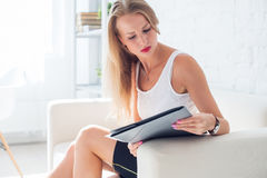 Portrait of business woman with folder sitting at office on sofa Stock Photos
