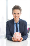 Portrait of business woman holding piggy bank Stock Photography