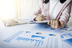 Portrait of business woman with laptop, finance graph and writes Royalty Free Stock Photos