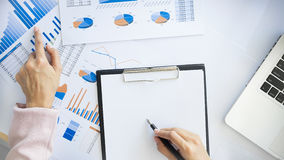 Portrait of business woman with laptop, finance graph and writes Stock Image