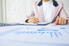 Portrait of business woman with laptop, finance graph and writes Royalty Free Stock Photography