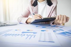Portrait of business woman with laptop, finance graph and writes Royalty Free Stock Image