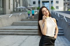 Portrait of business woman with mobile phone on city and office. Center background Stock Photos