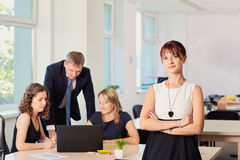 Portrait of business woman in the office in a chair on the background of working business partners. Stock Photo